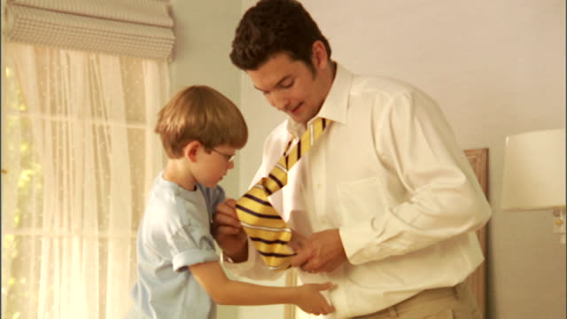 MS, ZI, Boy (6-7) helping father with tying tie