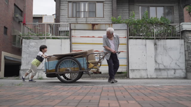 boy helping his grandfather pulling handcart, seoul, south korea - 小背心 個影片檔及 b 捲影像