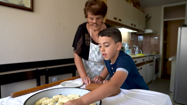 boy helping his grandma arrange rolls for baking - french food stock videos & royalty-free footage