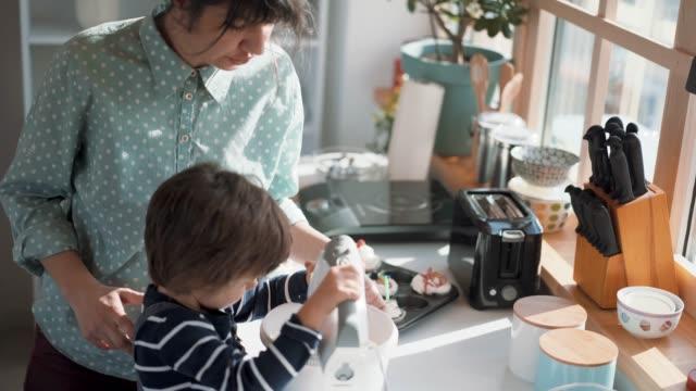 boy hilft seiner mutter beim mixen von gewhistter cream - haushaltsmaschine stock-videos und b-roll-filmmaterial