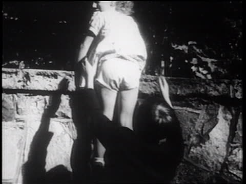 b/w 1939 rear view boy helping little girl off of stone wall / documentary - sister stock videos & royalty-free footage