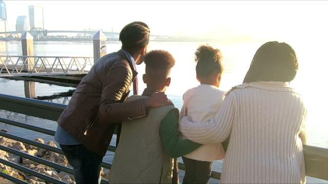 Chico ayuda hermana, los padres llegan en el paseo marítimo de la ciudad