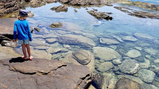 vídeos y material grabado en eventos de stock de niño haciendo senderismo en un lago rocoso cristalino búzios - un solo niño