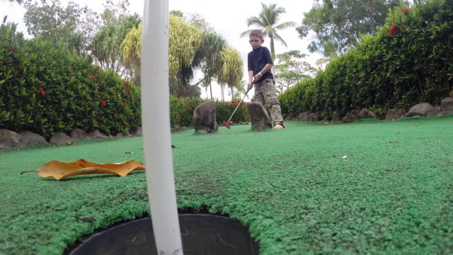 boy hits golf ball toward the hole on a mini golf green. - kind im grundschulalter stock-videos und b-roll-filmmaterial