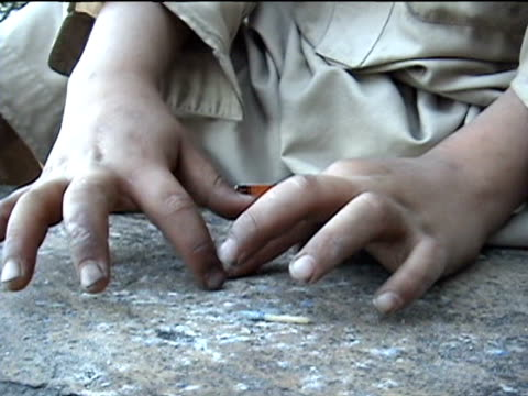 boy hitting head of matches with small piece of rock, making little explosions, swat district in tribal zone at afghan border, federally administered... - 男児のみ点の映像素材/bロール