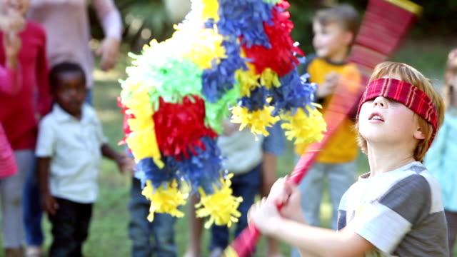 Boy hitting pinata, children watching in background