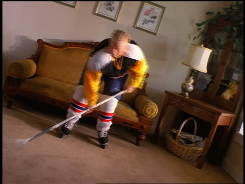 CANTED boy hockey player practicing in living room