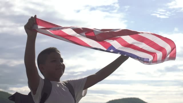 a boy holding american flag in the air blue sky - waving gesture stock videos & royalty-free footage