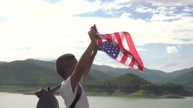 a boy holding american flag in the air blue sky with freedom - waving stock videos & royalty-free footage