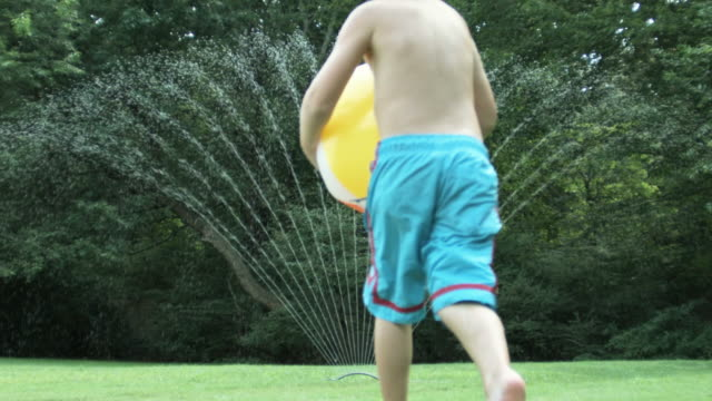 Boy holding beach ball and jumping through water from sprinkler