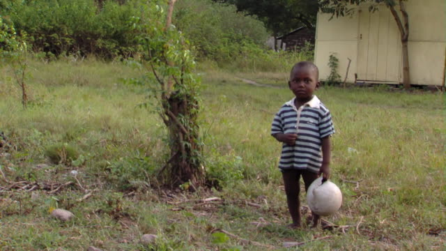 CU Boy holding broken ball standing in grass, Tamale, Ghana
