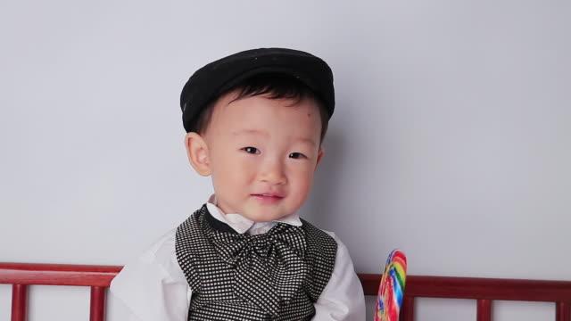 cu boy holding lollipop in hand and smiling / jeju, jeju-do, south korea - schiebermütze stock-videos und b-roll-filmmaterial
