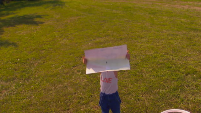 boy holding poster, standing in yard, jib shot - retro poster stock videos & royalty-free footage