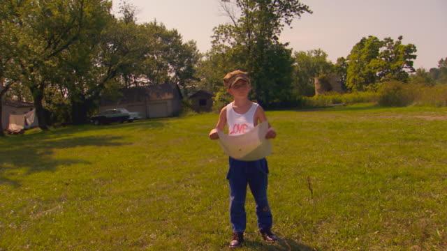 vídeos y material grabado en eventos de stock de boy holding poster, standing in yard - articulación humana