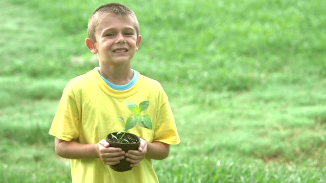 Boy holding potted plant for the garden