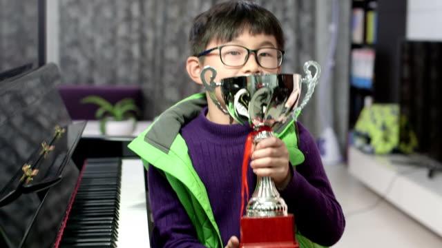 jongen zilver cup te houden door de piano