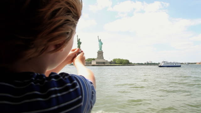 ms zi boy (10-11) holding souvenir of statue of liberty in air to measure with the real one in the distance / new york city, new york, usa - discovery stock videos & royalty-free footage