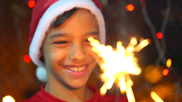 boy holding sparkler light in the christmas night - light natural phenomenon stock videos & royalty-free footage