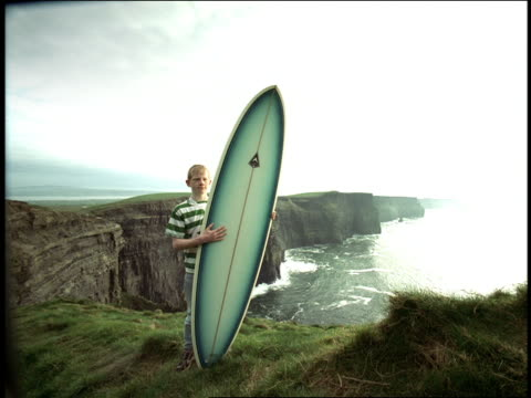stockvideo's en b-roll-footage met portrait boy holding surfboard standing at edge of cliffs by ocean / cliffs of moher, ireland - surfbord