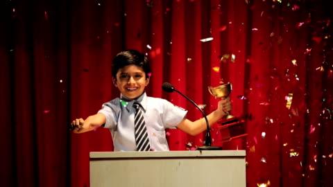 ms boy holding trophy celebrating the success at annual day - vinna bildbanksvideor och videomaterial från bakom kulisserna