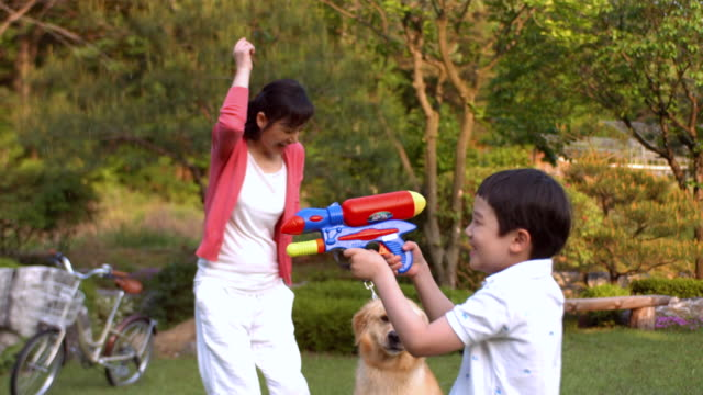 ms slo mo ts boy holding water gun and getting soaked with mommy / seoul, south korea - squirt gun stock videos and b-roll footage