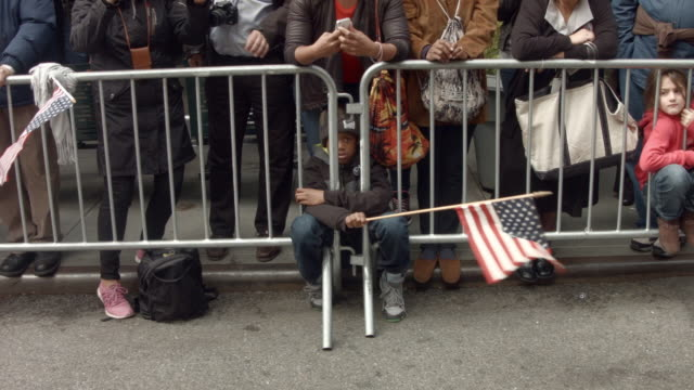 a boy holds up a flag as veterans soldiers their families and others march in the annual the veteran's day parade along fifth avenue on november 11... - young war veteran stock videos & royalty-free footage
