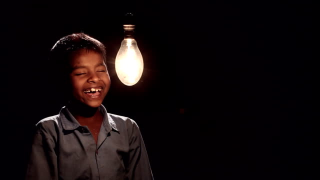 stockvideo's en b-roll-footage met boy illuminated a electric bulb - electric lamp