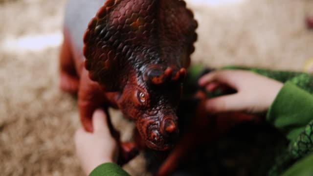 vídeos de stock, filmes e b-roll de menino em uma fantasia de dinossauro brincando com seus dinossauros - jurássico