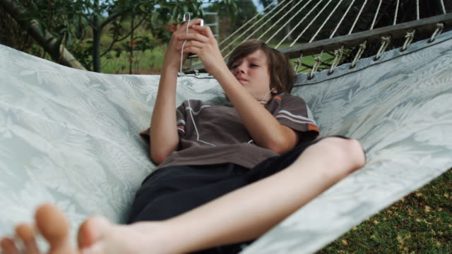 boy in a hammock listening to an mp3 player - one teenage boy only stock videos & royalty-free footage