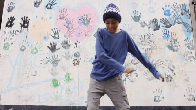 boy in a knit hat dancing in backyard - 頭にかぶるもの点の映像素材/bロール