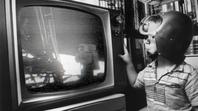 vídeos de stock e filmes b-roll de a boy in a space helmet stares at a television broadcast of astronaut neil armstrong on the moon. - lua