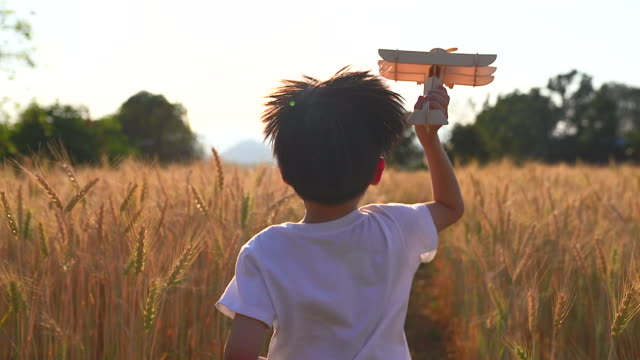 a boy in a white shirt holds a toy plane running in the wheat field he used his imagination to think that he was a pilot. run freely in the wheat fields. - imagination stock videos & royalty-free footage