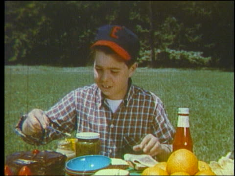 1960 boy in baseball cap putting condiment on bread at picnic table - baseball cap stock videos & royalty-free footage