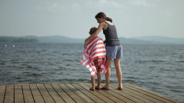 ms boy in beach towel with his mother standing on dock looking out to lake / wolfebro, nh, usa     - towel stock videos & royalty-free footage