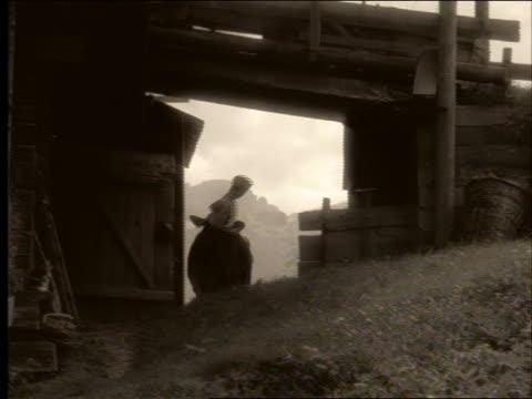stockvideo's en b-roll-footage met sepia pan boy in cap + suspenders leading cow under barn - kleurtoon
