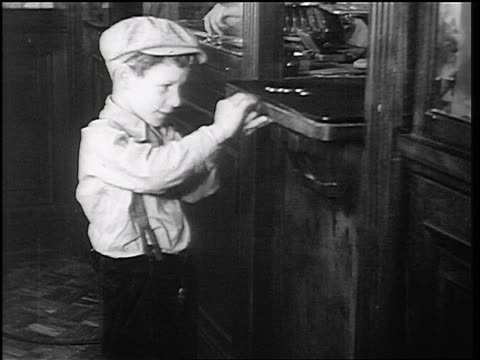 b/w 1934 boy in cap taking coins at teller window in fon du lac bank / east peoria, il / newsreel - cashier stock videos & royalty-free footage
