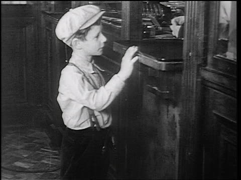 B/W 1934 boy in cap withdrawing coins from teller in Fon du Lac bank / East Peoria, IL / newsreel