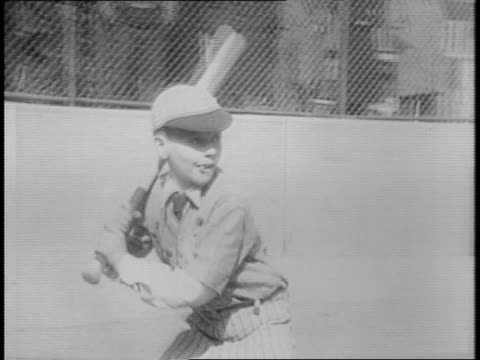 boy in catcher's equipment talking to pitcher / montage of chubby boy at bat with 'children's aid society' banner behind plate boy hitting ball and... - baseballmannschaft stock-videos und b-roll-filmmaterial