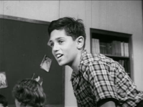 b/w 1951 boy in classroom preparing to throw paper airplane / educational - 1951 stock videos & royalty-free footage