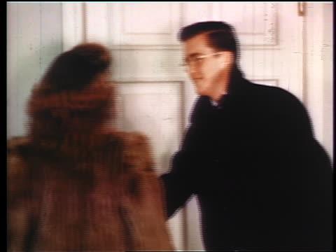 1945 boy in coat opening door for date in fur coat / industrial