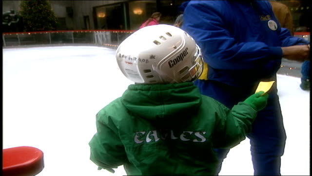 boy in eagles jacket giving ticket to ice skate rockefeller center - philadelphia eagles stock videos & royalty-free footage