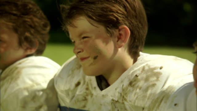 CU, Boy (6-7) in football gear in field
