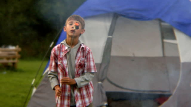 ms boy in front of tent blowing on flaming marshmallow on end of stick/ bovina, new york - children only stock videos & royalty-free footage
