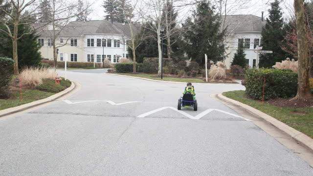 Boy in gocart drives down residential road into the distance.