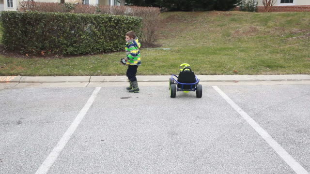 Boy in gocart parked in parking space exits vehicle and sister steps in and brother offers his gloves and Dad checks gocart.