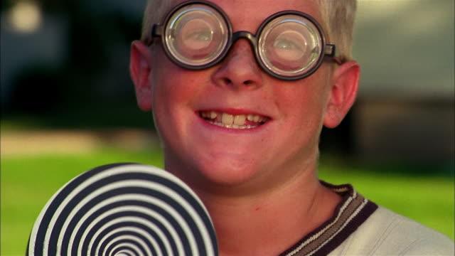 a boy in goggles spins a hypno-wheel. - dizzy stock videos & royalty-free footage