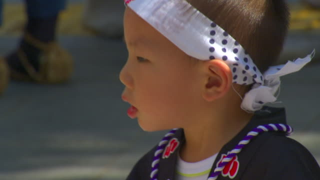 cu selective focus boy in hachimaki looking up at passing adults at autumn festival, shibuya, tokyo, japan - hair accessory stock videos and b-roll footage