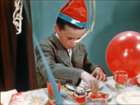 1946 boy in hat being handed cake at birthday party + starts eating it / industrial - party hat stock videos & royalty-free footage