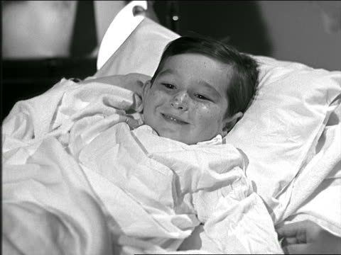 B/W 1948 boy in hospital bed has tonsils checked with tongue depressor