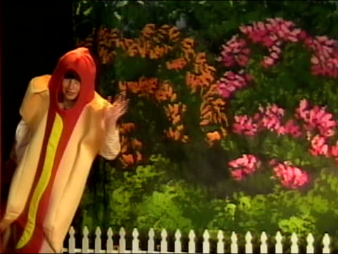 stockvideo's en b-roll-footage met boy in hot dog costume waving at camera from side of stage / los angeles, california - gluren